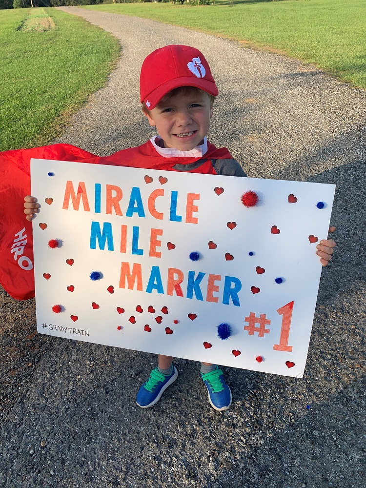 Grady holding mile marker sign photo